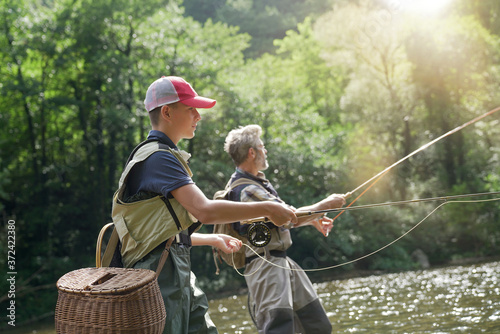A father and his son fly fishing in summer on a beautiful trout river with clear Fototapeta