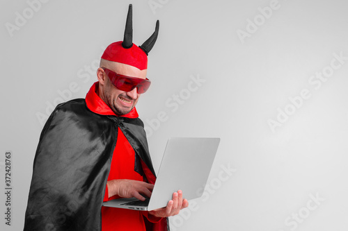 Valokuvatapetti Stylish caucasian man in devil hat with horns and vampire cape with laptop isolated on white backhround