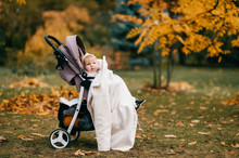 Pretty Little Baby With Red Hair, Big Blue Eyes, Pump Lips In A Stroller On The Street In The Fall