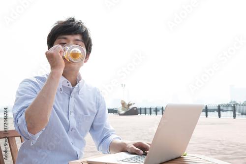 ビールを飲みながらパソコンをする男性 Slika na platnu
