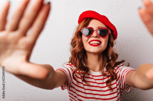 Fotografiet Blithesome caucasian girl in red beret having fun in studio