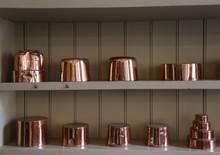 Shiny Copper Pots And Pans Sit...