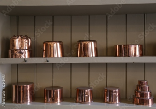Canvastavla Shiny copper pots and pans sitting on a wooden shelf in an old kitchen
