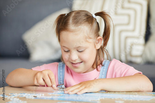 Little girl with down syndrome sitting at the table and learning to collect puzz Fototapeta