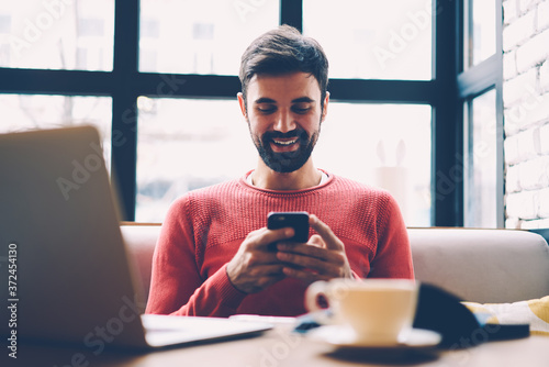 Fotografie, Obraz Smiling bearded hipster guy sending feedback on smartphone chatting with friend