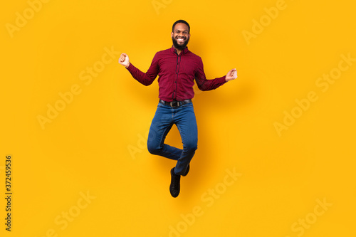 Photo Happy black guy jumping and looking at camera