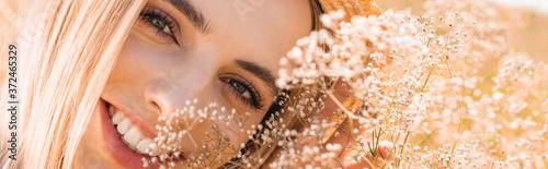 Canvastavla portrait of sensual blonde woman looking at camera near wildflowers, horizontal