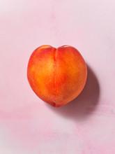 A Single Whole Peach On A Pale...