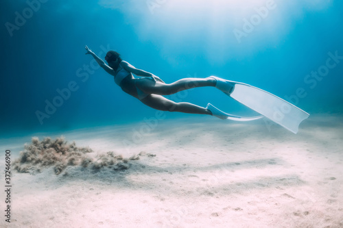 Attractive woman freediver glides and posing over sandy bottom with fins Poster Mural XXL