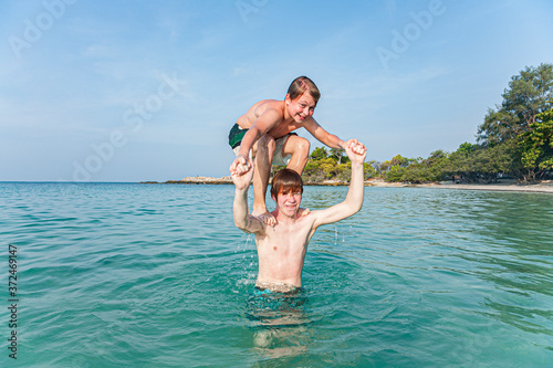 Obraz na plátně brothers are playing together in a beautiful sea with crystal clear water