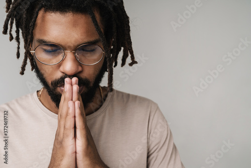 Photo Praying african guy isolated over grey wall