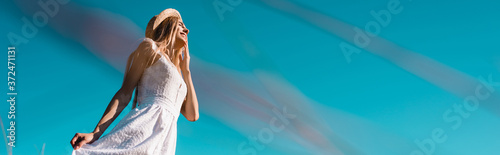 Fototapeta selective focus of young woman touching white dress against blue sky, panoramic