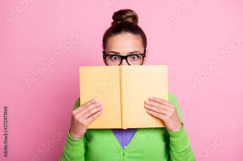 Obraz na plátne Photo of astonished worried student girl close cover text book her lips impresse