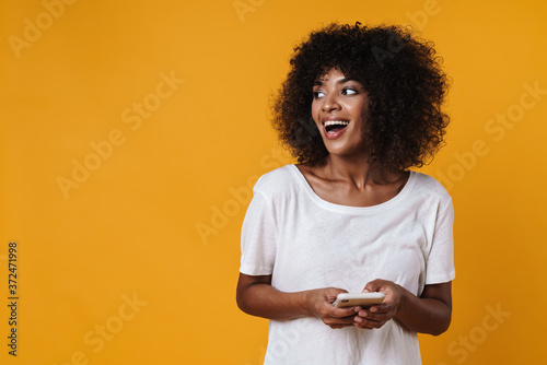 Image of happy african american girl smiling and using mobile phone