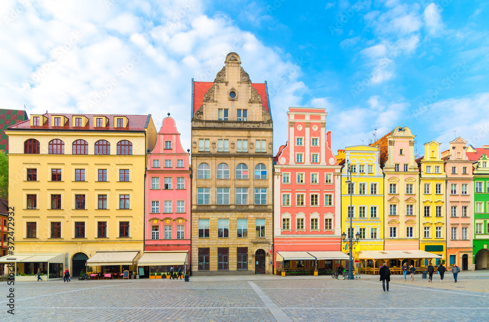 Fototapeta Row of colorful traditional buildings with multicolored facades on cobblestone Rynek Market Square in old town historical city centre of Wroclaw, blue sky background, Poland