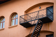 An Emergency Escape Staircase Outside The Classic Europe Style Orange Colorful Building.