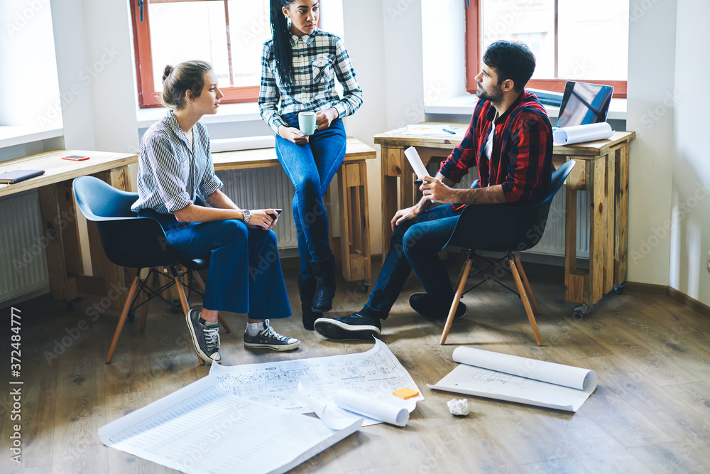 Fototapeta Cropped image of skilled students discussing teamwork on new architectural sketch sitting indoors in stylish design studio.Pensive male and female professional architects collaborating on blueprint