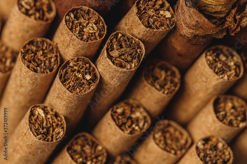 Pile of new cigars close up on wooden table