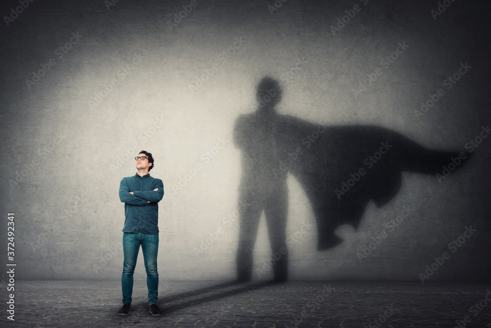 Fototapeta Brave man keeps arms crossed, looks confident, casting a superhero with cape shadow on the wall. Ambition and business success concept. Leadership hero power, motivation and inner strength symbol.
