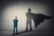 canvas print picture Brave man keeps arms crossed, looks confident, casting a superhero with cape shadow on the wall. Ambition and business success concept. Leadership hero power, motivation and inner strength symbol.
