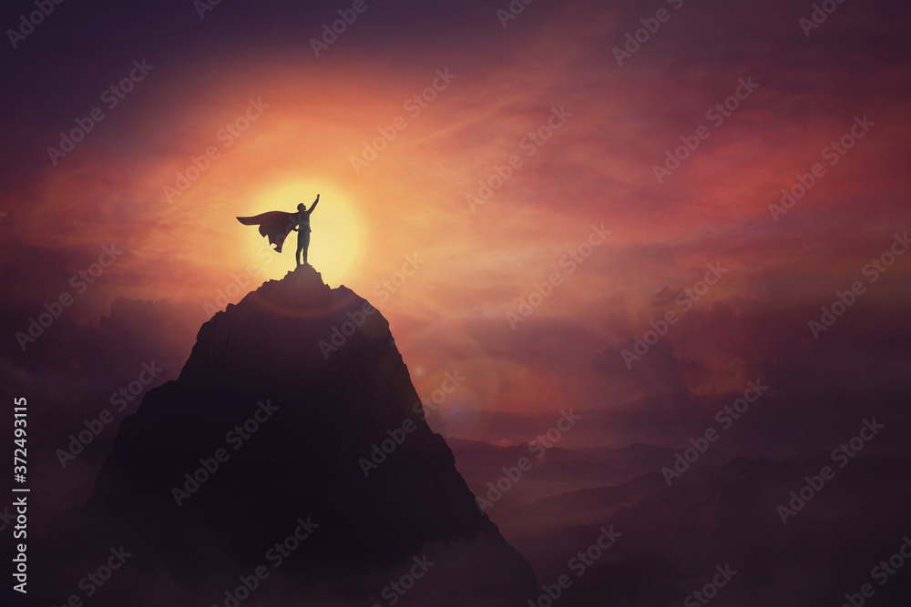 Fototapeta Conceptual sunset scene, superhero with cape standing brave on top of a mountain looks determined at horizon raising one hand up as a winning leader. Hero power and motivation, overcoming obstacles.