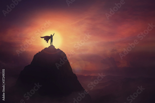 Fotografiet Conceptual sunset scene, superhero with cape standing brave on top of a mountain looks determined at horizon raising one hand up as a winning leader