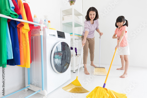 Fotografia family mother and child girl cleaning floors in house with broom and mop
