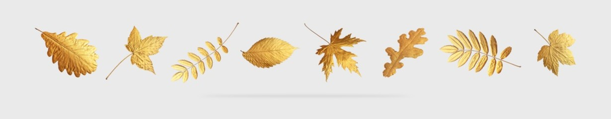 Golden flying autumn leaves of different shapes on light gray background. Autumn concept, fall background. Minimal floral design, autumn leaf frame. Golden twig. Autumn creative composition