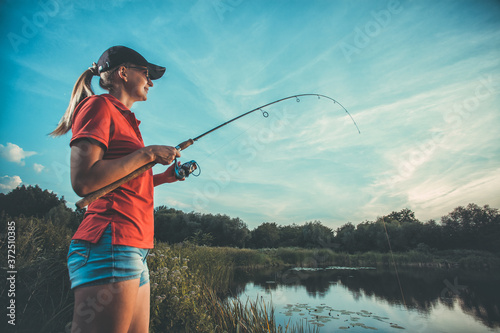 Fotografie, Obraz Cute caucasian woman is fishing with rod on the summer lake