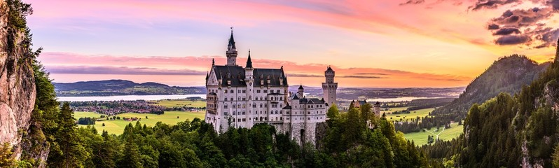 A beautiful and colourful sunrise over the famous Neuschwanstein Castle in Germany. It is a 19th-century Romanesque Revival palace on a rugged hill above the village of Hohenschwangau near Füssen.