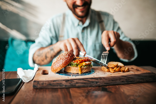 Tablou Canvas Handsome middle age man sitting in restaurant and enjoying in delicious burger