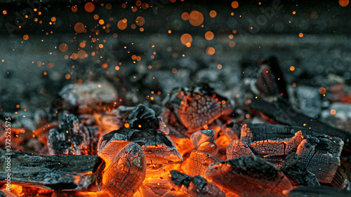Photo Barbecue Grill Pit With Glowing And Flaming Hot Charcoal Briquettes, Close-Up