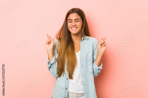 Young slim woman crossing fingers for having luck Canvas Print