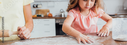 Tablou Canvas cropped view of mother standing near daughter scattering flour on wooden table i