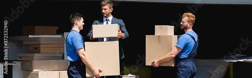Fotografija Horizontal crop of loaders holding carton boxes near businessman in warehouse ou