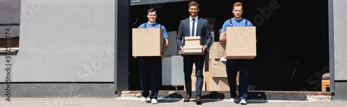 Panoramic shot of movers and businessman holding carton boxes beside warehouse o Slika na platnu