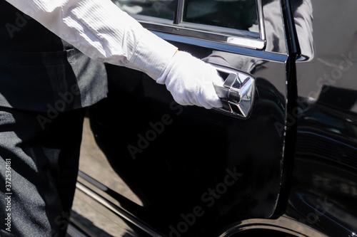 Fotografie, Obraz ハイヤー(タクシー)の乗務員がドアに手をかけて、開けようとしているシーン