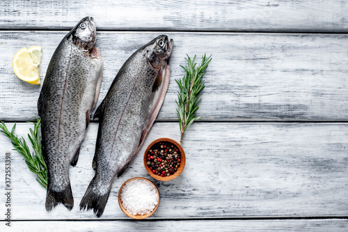 Fotografie, Obraz Raw trout fish with spices and ingredients on wooden background with copy space