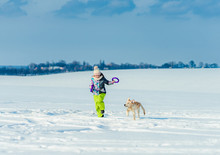 Girl Running With Dog In Snow