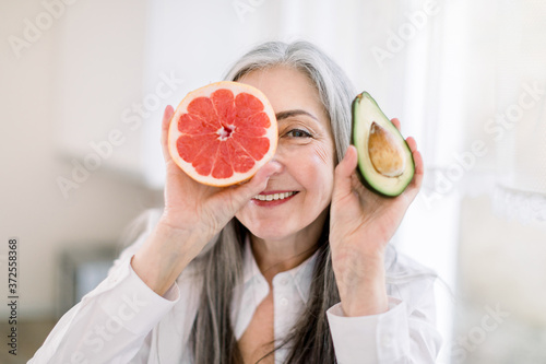 Photo Close up portrait of senior gray haired woman in the kitchen, holding fresh avocado and grapefruit peaces, smiling to camera hiding her eye