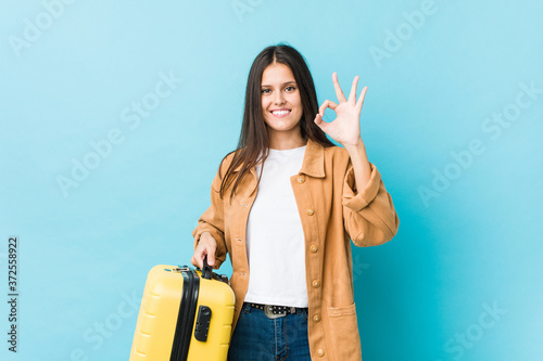 Young caucasian woman holding a suitcase cheerful and confident showing ok gesture.