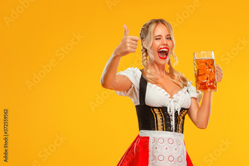 Photo Young sexy Oktoberfest girl waitress, wearing a traditional Bavarian or german dirndl
