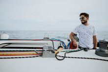 Smiling Young Man Wearing Sunglasses Standing In Sailboat Against Sky