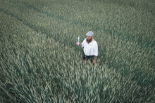 Drone Shot Of Man Holding Small Windmill While Standing Amidst Cornfield