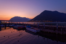 Italy, Lombardy, Sulzano, Boats And Pier On Lake Iseo At Sunset
