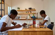 Young Couple Studying On Table While Sitting At Home