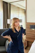 Thoughtful Chambermaid With Hands On Hip Standing In Hotel Room