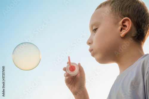 Papel de parede Boy blowing soap bubble on the blue sky background