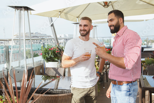 Fotografie, Obraz Two handsome stylish men talking over drinks at modern rooftop restaurant, copy