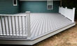 New composite deck on the back of a house with green vinyl siding.